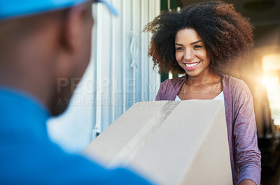 Buy stock photo Shot of a postal worker delivering a package to a young female customer
