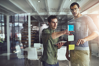 Buy stock photo Cropped shot of two young designers planning on a glass board