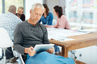 Buy stock photo Shot of a handsome mature man using his tablet while sitting in the boardroom during a meeting