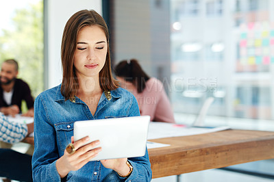 Buy stock photo Shot of an attractive young woman using her tablet while sitting in the boardroom during a meeting