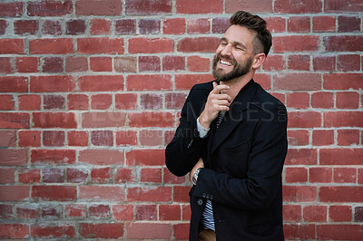 Buy stock photo Cropped shot of a handsome young man looking thoughtful while standing against a brick wall outside