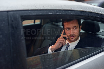 Buy stock photo Shot of a businessman sitting in the backseat of a car talking on his cellphone