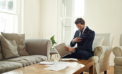 Buy stock photo Shot of a consultant sitting on a chair in his client's living room