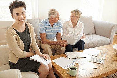 Buy stock photo Portrait of a smiling financial advisor sitting with a senior couple in their living room