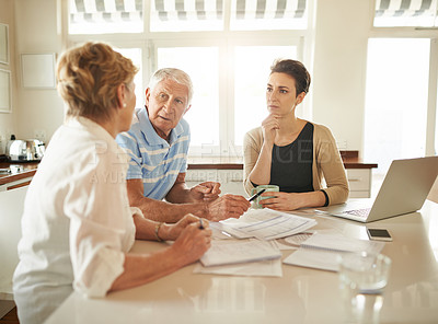 Buy stock photo Shot of a senior couple getting advice from their financial consultant in their kitchen