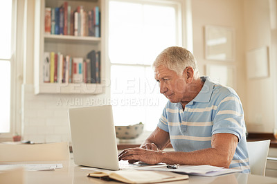 Buy stock photo Shot of a senior man sitting in his kitchen using a laptop to take care of the household finances