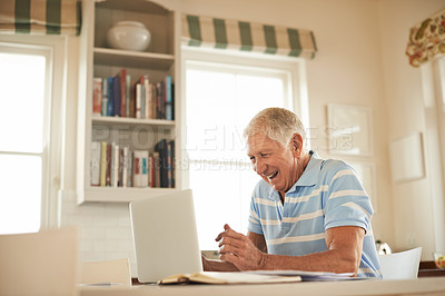 Buy stock photo Shot of a smiling man using a laptop while sitting in his kitchen