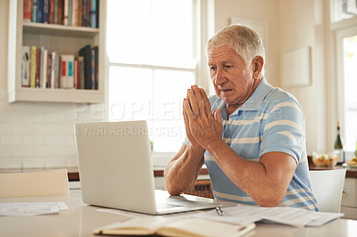 Buy stock photo Shot of a senior man looking stressed while doing the household finances on a laptop in his kitchen