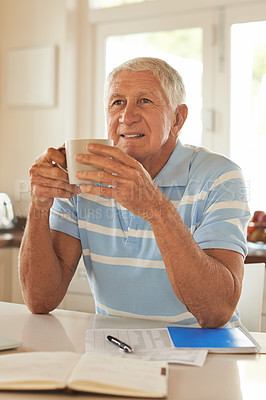 Buy stock photo Cropped shot of a smiling senior man deep in thought while drinking a coffee in his kitchen