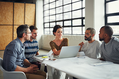 Buy stock photo Shot of a group of designers using a laptop in their meeting