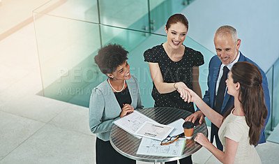 Buy stock photo Cropped shot of a group of businesspeople shaking hands during a meeting in an office