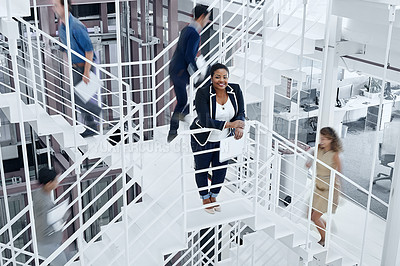 Buy stock photo Portrait of a young professional standing on a stairs with colleagues rushing around her
