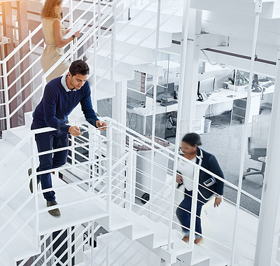 Buy stock photo Shot of a young professional standing on a stairs with colleagues rushing around him