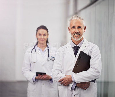 Buy stock photo Portrait of a mature male doctor standing in a hospital with his colleague in the background