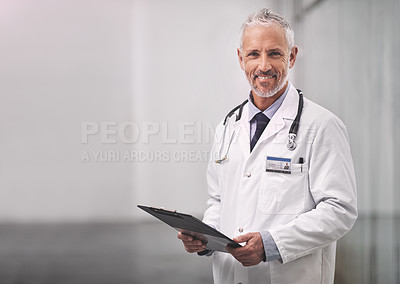 Buy stock photo Portrait of a mature male doctor standing with a clipboard in a hospital