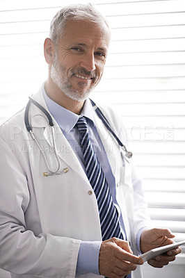 Buy stock photo Portrait of a mature male doctor using a digital tablet