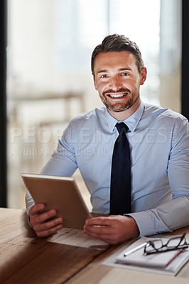Buy stock photo Portrait of a smiling businessman using a digital tablet in an office