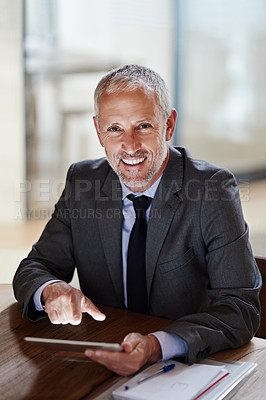 Buy stock photo Shot of a smiling mature businessman using a digital tablet in an office