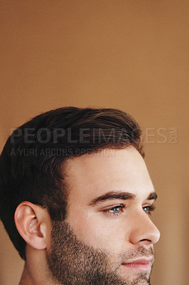 Buy stock photo Cropped shot of a handsome young man with dark hair and light eyes against a brown background