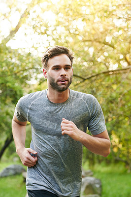 Buy stock photo Cropped shot of a young man out for a run in the park