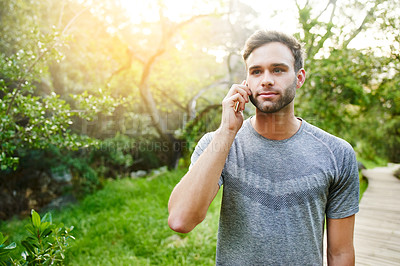 Buy stock photo Cropped shot of a young man talking on his cellphone while out in a park