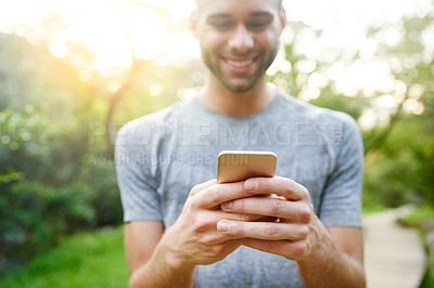 Buy stock photo Cropped shot of a young man texting on his cellphone while out in a park