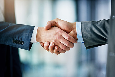 Buy stock photo Closeup shot of two businessmen shaking hands in an office