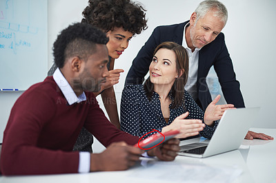 Buy stock photo Cropped shot of a group of businesspeople discussing something on a laptop