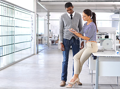 Buy stock photo Shot of two colleagues talking together over a digital tablet while standing together in an office
