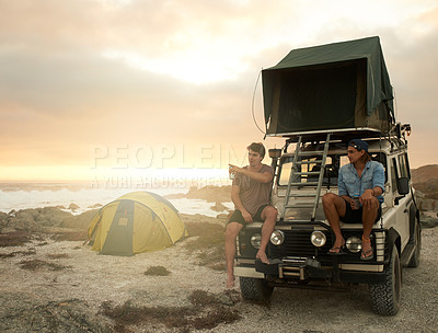 Buy stock photo Shot of two friends sitting on the hood of their off road vehicle on a coastal camping trip