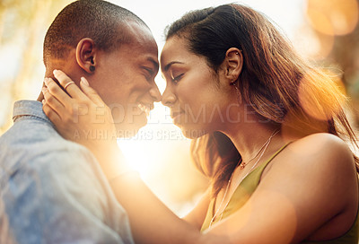 Buy stock photo Shot of an affectionate young couple sharing a tender moment outdoors