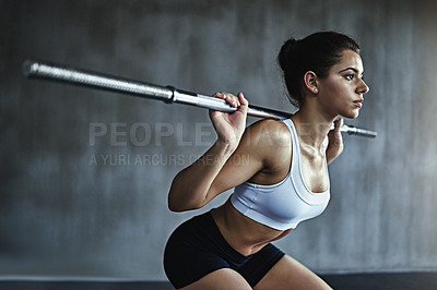 Buy stock photo Shot of a sporty young woman working out with a steel bar at the gym