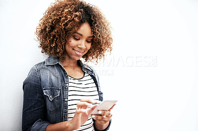 Buy stock photo Cropped shot of a young woman using her cellphone against a white background