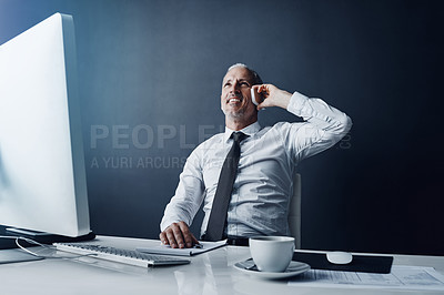 Buy stock photo Cropped shot of a mature businessman making a call while working on his computer