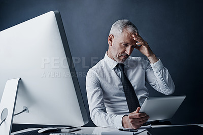Buy stock photo Cropped shot of a mature businessman looking stressed working on his tablet
