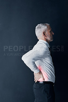 Buy stock photo Studio shot of a mature businessman holding his back in pain