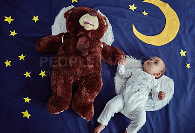 Buy stock photo Concept shot of an adorable baby boy and a teddy bear wearing angel wings against an imaginary night time background