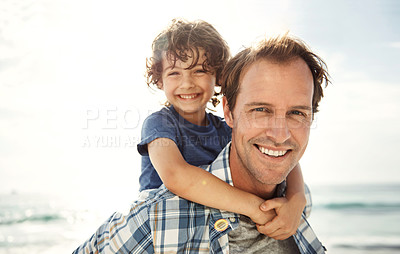 Buy stock photo Portrait of a father and his young son enjoying a day at the beach