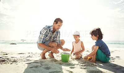 Buy stock photo Shot of a father building a sandcastle on the beach with his two young children