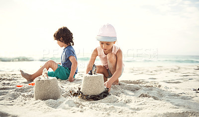Buy stock photo Shot of two young siblings playing together in the sand on the beach