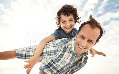 Buy stock photo Portrait of a father and son enjoying a piggyback ride on the beach