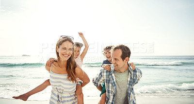 Buy stock photo Shot of a happy young family having fun at the beach