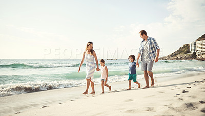 Buy stock photo Shot of a young family holding hands while walking on the beach