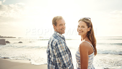Buy stock photo Portrait of a smiling mature couple spending time together at the beach at sunset