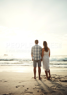 Buy stock photo Rearview shot of a mature couple standing hand in hand together watching the sunset at the beach