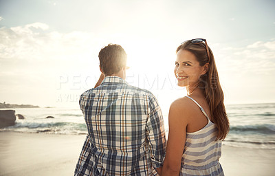 Buy stock photo Portrait of a smiling woman standing with her husband at the beach at sunset
