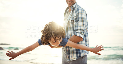 Buy stock photo Shot of a father playing with his young son on the beach