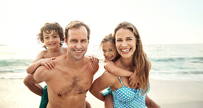 Buy stock photo Portrait of two parents carrying their little son and daughter on their backs at the beach in the late afternoon