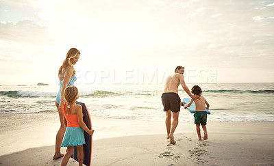 Buy stock photo Shot of two parents taking their little son and daughter wakeboarding at the beach in the late afternoon