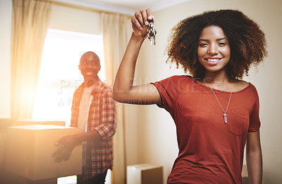 Buy stock photo Portrait of a young woman holding up the keys to a new home with her boyfriend in the background